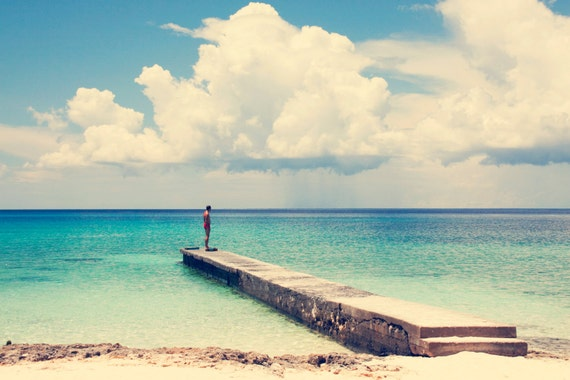 Beach landscape in Maria la Gorda, Cuba. Sunny and lighty day with a calm sea. Lonely man on wooden bridge. 8x10 photograph.