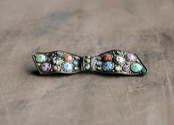 silver bow brooch with light colored polka dots