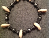 Hematite and cowry shell beads. Fits most wrists. (Male)