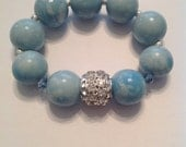 Sky blue glass bracelet with rhinestone charm.  Fits most wrists.