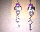 A short dangle with a Flat european bead mixed with pink and silver accented with silver toned keys.