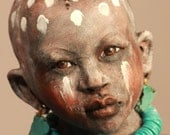 African boy sculpture with tribal decorations and turquoise
