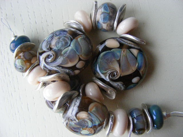 set of handmade beads with soft peach and silvered glass