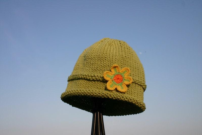 کودک کلاه بافتنی -- کلاه سبز دست بچه گره را با گل زرد