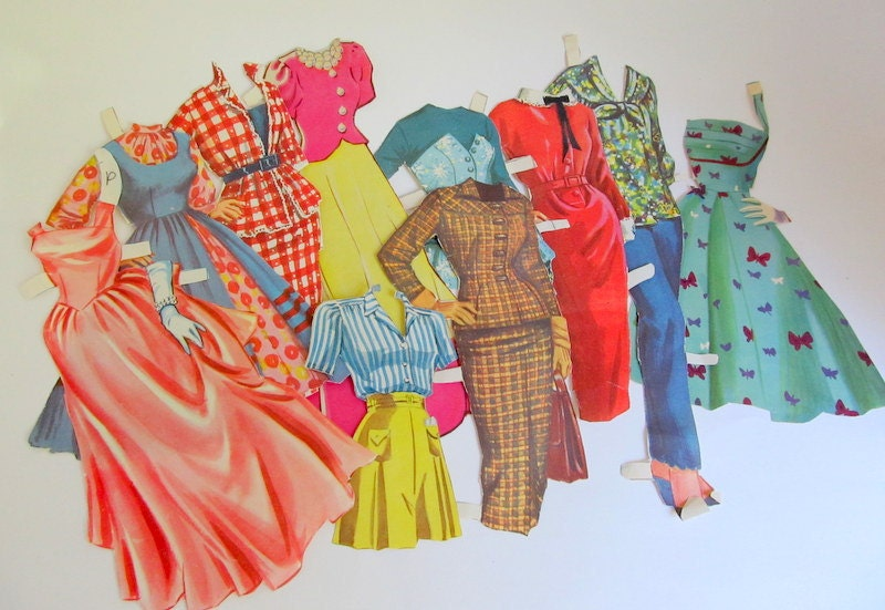 Several vintage paper dolls outfits including paper doll dresses and trousers