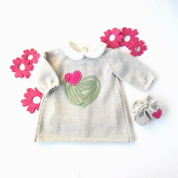 A knitted baby dress with felt hearts