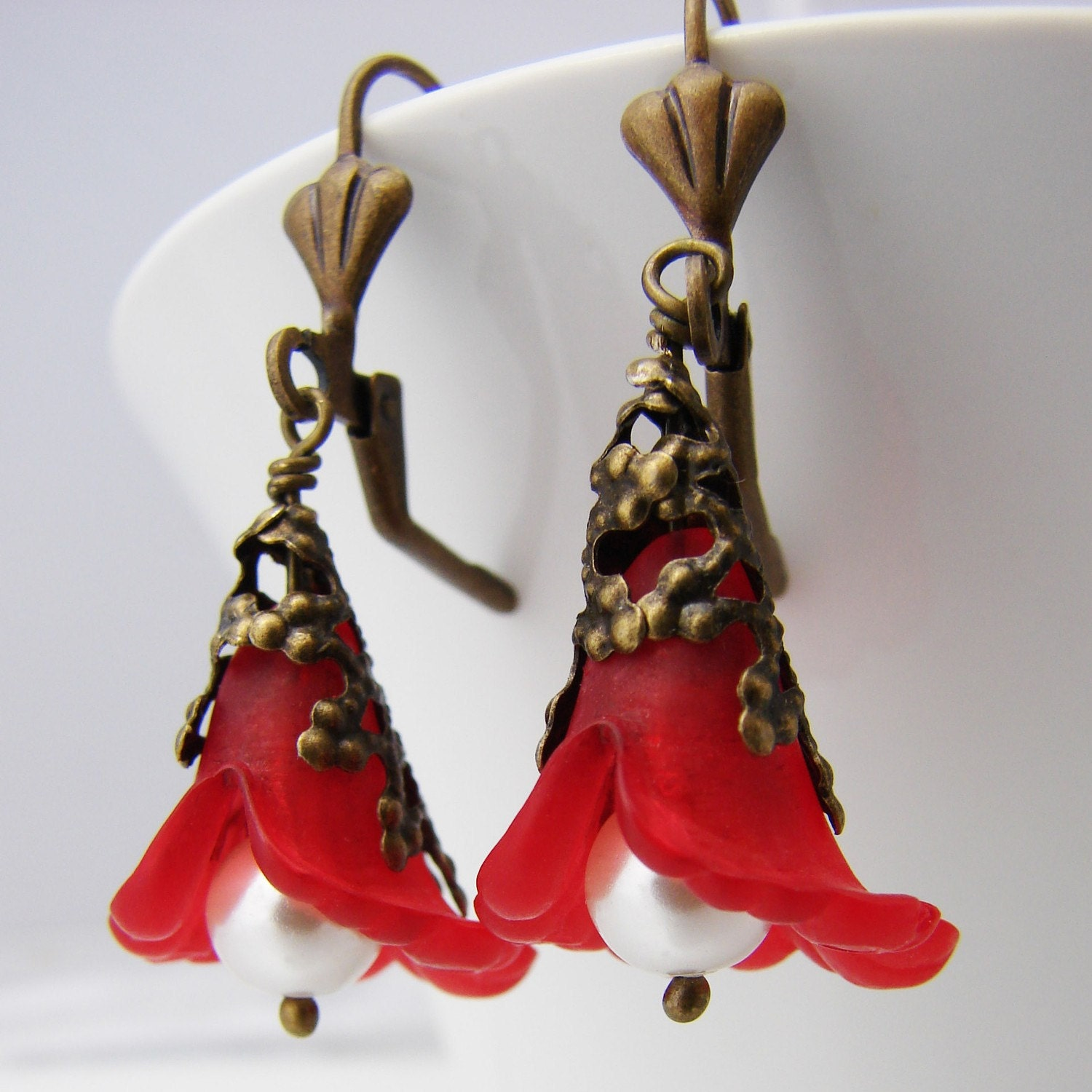 Red lucite flower drop earrings on antiqued brass earwires