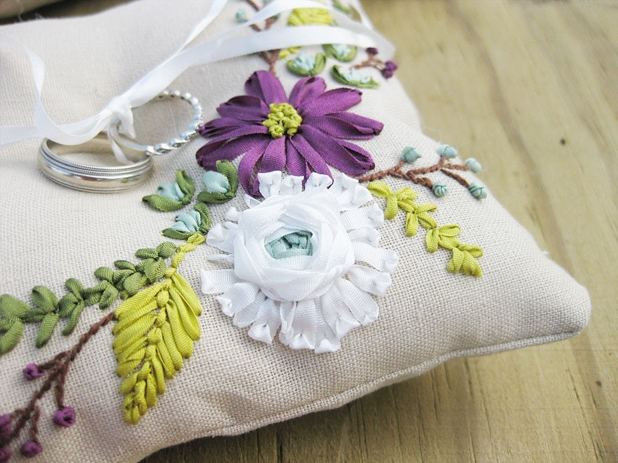Ring pillow with ribbon embroidered flowers in white, purple, and blue.