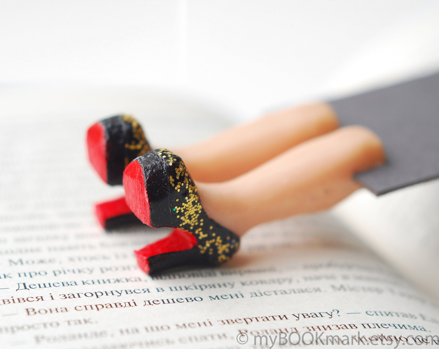 Louboutin shoes bookmark with golden glitter. Legs in book. Elegant black high fashion gift. Gold and red shoes. Valentine for her
