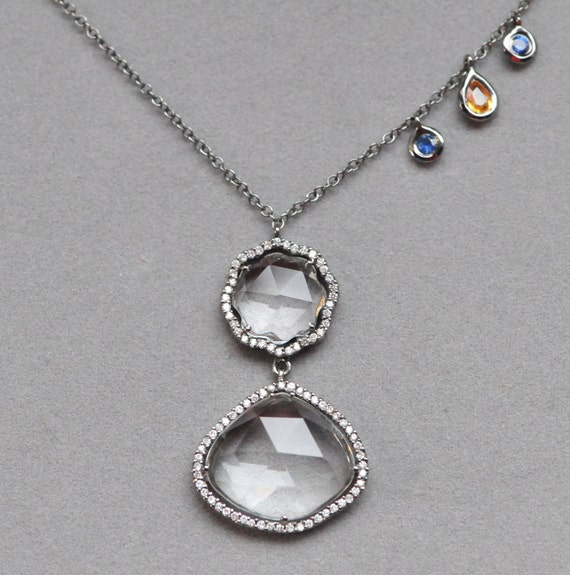 pave diamond black rhodium pendant with white topaz and sapphire in 18k gold