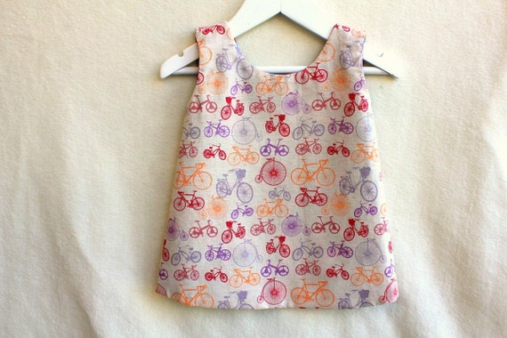 Girl's Reversible Pinafore. Made to Order, Size NB - 5/6. Funky Flowers and Bikes. Designer Print.